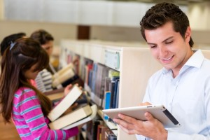 Man with an e-book reader while his friends look for books at th