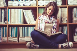Full length of a female student sitting against bookshelf and re