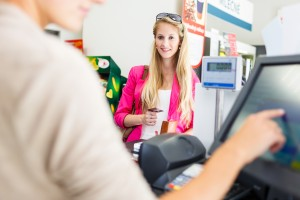 Beautiful young woman paying for her groceries at the counter of