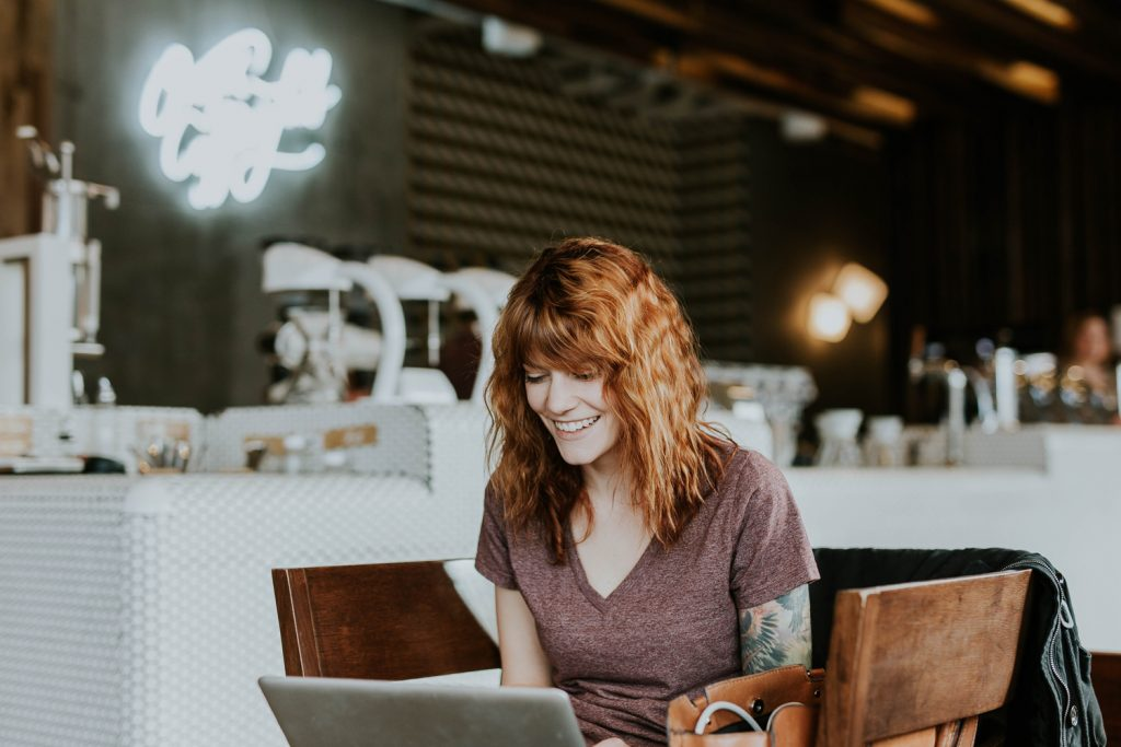 Woman online shopping in a brick and mortar coffee shop